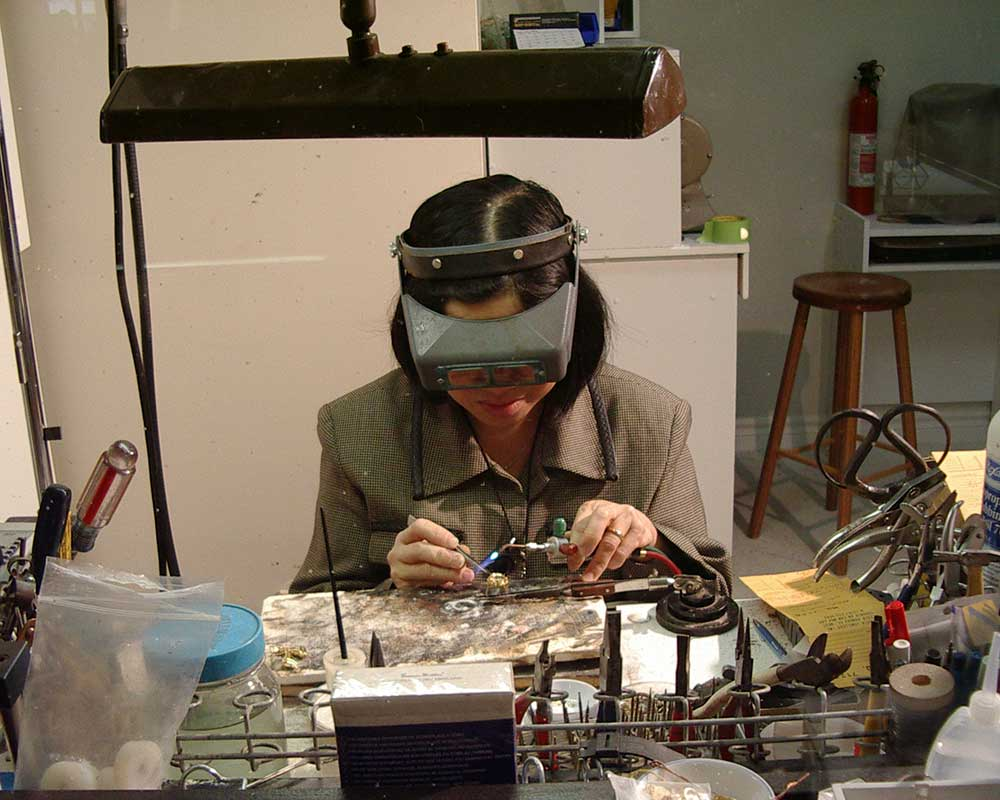 a women sits at a desk repairing jewellery